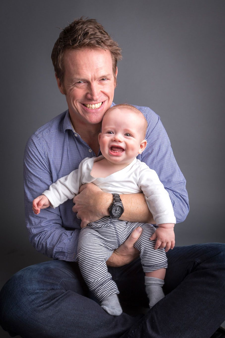 Portrait of a baby boy and his dad in a studio with backdrop and lighting equipment